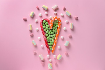 Composition with tasty candies on color background