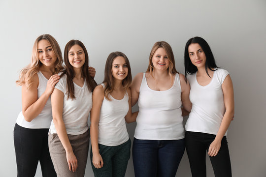 Beautiful young women on light background. Concept of body positivity