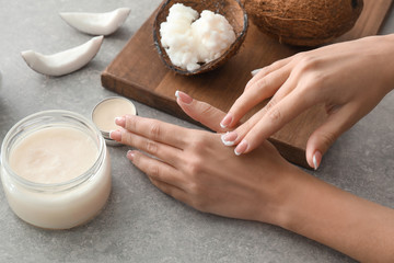 Woman applying coconut oil onto skin on grey background
