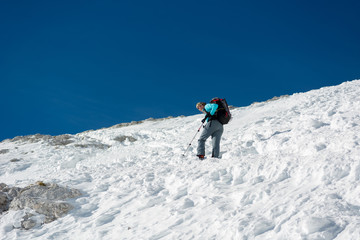 Female alpinist ascending a steep snowy slope.