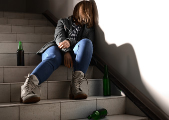 Unconscious young woman with empty bottles sitting on stairs. Concept of alcoholism