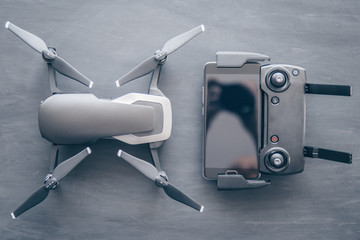 Wall Mural - Innovation photography concept. Mate color. A new black drone on a black table. The concept of using drones in life and industry. Top view Remote and smartphone macro Details. Copy space.