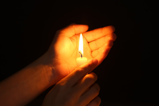 Female hands with burning candle in darkness