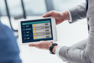 partial view of businessman holding digital tablet with sport bets app on screen