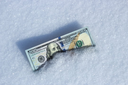 American currency lies in the snow