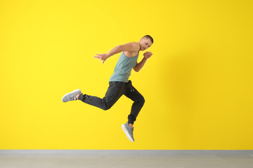 Young male dancer jumping near color wall