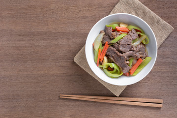 top view of stir fried beef with banana pepper in a ceramic bowl on wooden table. hot and spicy homemade style food concept.