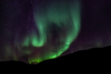 Amazing Aurora Borealis in North Norway (Kvaloya), mountains in the background