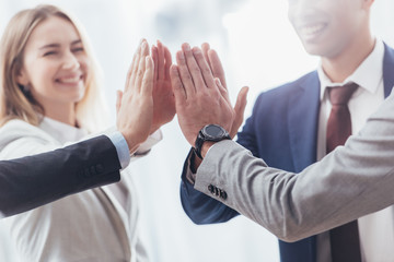cropped shot of professional successful business team giving high five in office