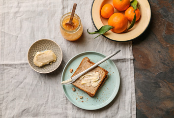Bread with butter and tasty tangerine jam on table