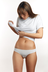 Unrecognizable woman in underwear testing fat layer on waist. Perfect slim tanned body - an example of sports, dieting, fitness or plastic surgery and aesthetic cosmetology