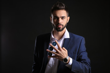 Handsome young man with poker chips on dark background
