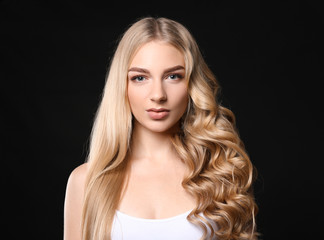 Beautiful young woman with straight and curled hair on dark background