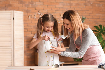 Happy mother with daughter cooking pastry in kitchen at home