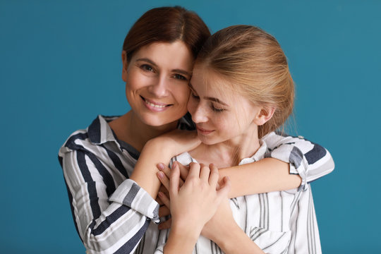 Portrait of happy mother and daughter on color background