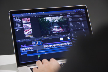 Video editing with laptop. Professional editor adding special effects or color grading footage for commercial film or movie.