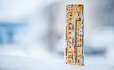 Thermometer on snow shows low temperatures in celsius or farenheit