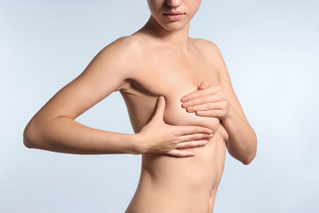 Young woman checking her breast on light background. Cancer awareness concept