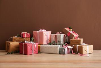 Festive gift boxes on table against color background