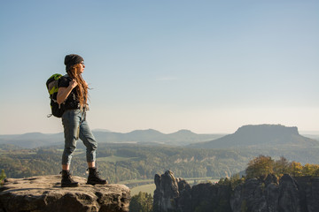 Young woman traveler with baclpack stand on the cliff in mountains