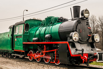 A green steam locomotive engine on display in Marki, Poland. The narrow gauge train PX48 was manufactured in 1953 for the 750mm commuter railway.