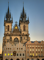 Church of Our Lady before Týn, an ornate gothic medieval catholic church with towers and spires, behind cafes in the Old Town Square, Prague, Czech Republic with golden sunset reflected in the windows
