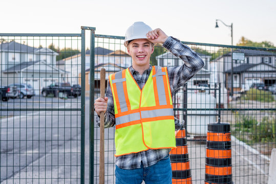 Happy young construction worker standing on a job site and holding a shovel.