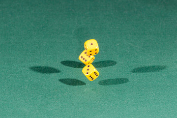 Three yellow dices falling on a green table