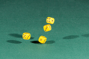 Four yellow dices falling on a green table