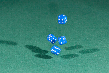 Four blue dices falling on a green table