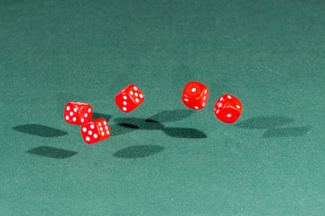 Five red dices falling on a green table