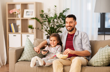 family, fatherhood and people concept - happy father and daughter with popcorn watching tv at home