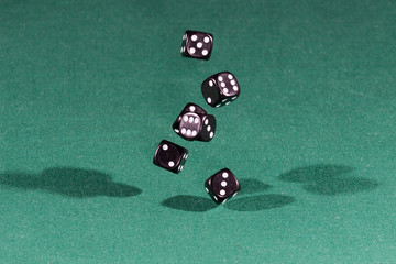 Six black dices falling on a green table