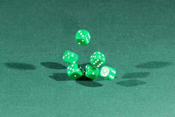 Six green dices falling on a green table