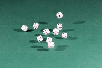 Ten white dices falling on a green table