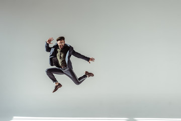 bearded man in cap and glasses jumping high on grey background