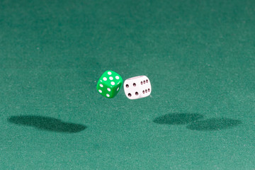 Two white and green dices falling on a green table