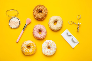 Composition with sweet tasty donuts, cosmetics and accessories on color background
