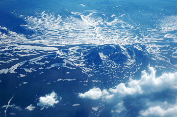 Mountains, snow and clouds from the height of the plane