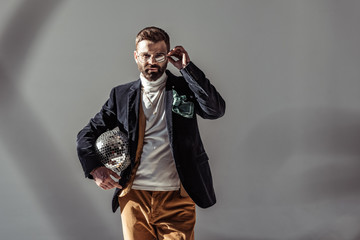 bearded man touching glasses, holding mosaic disco ball and looking at camera on grey background