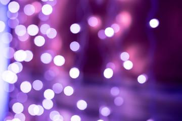 Purple bokeh blurred lights background. Violet garlands decoration for the new year celebration.