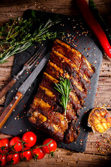 Rustic vintage wooden table, black rectangular stone stand for fried juicy pork ribs with meat, spices, fork and knife, pepper, rosemary, thyme, basil, cherry tomatoes are scattered dark background