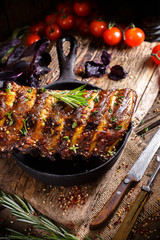 Rustic vintage wooden table, in a pan of fried juicy pork ribs with meat, spices, fork and knife, pepper, rosemary, thyme, basil, cherry tomatoes, dark background, mustard