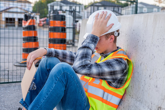 Upset and frustrated construction worker sitting down at a job site.