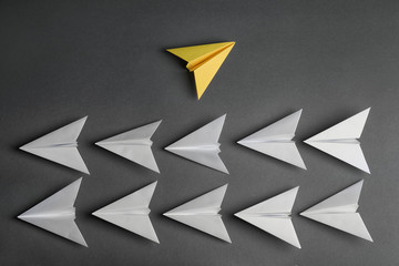 Different color paper plane flying away from others on dark background, top view