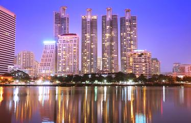 City skyline at night Bangkok buildings over river panorama.