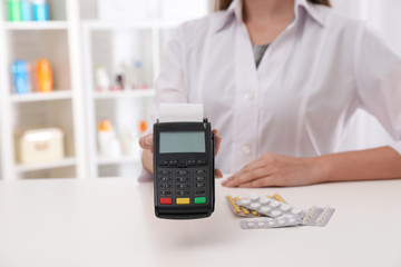 Pharmacist with payment terminal and pills in drug store, closeup. Space for text