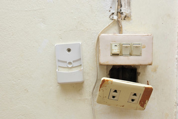 a light switch and electrical socket switch with damaged wiring on the wall