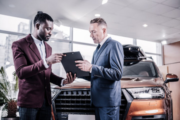 Businessman signing contract while buying new brown hatchback car