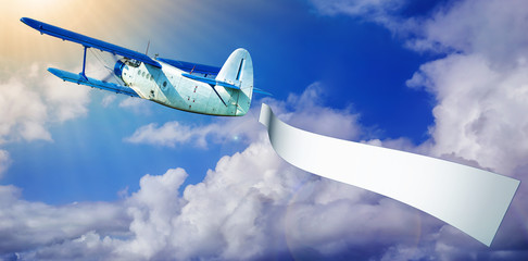 airplane with a banner against a blue sky